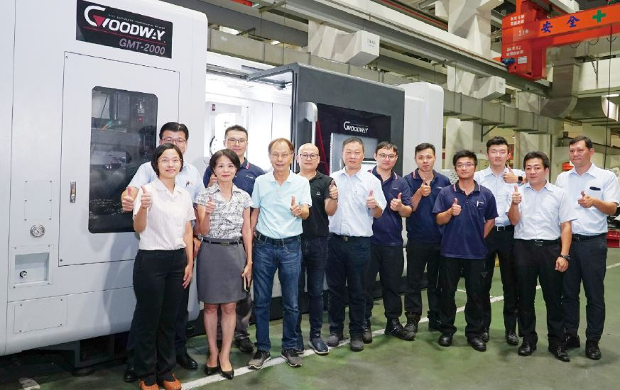 The Group Photo of Chairman of Goodway, Edward Yang (3rd from the left in the front row) and Team of Anti-Counterfeiting Roller for Mask, Standing in front of Goodway GMT 2000Y CNC Lathe.